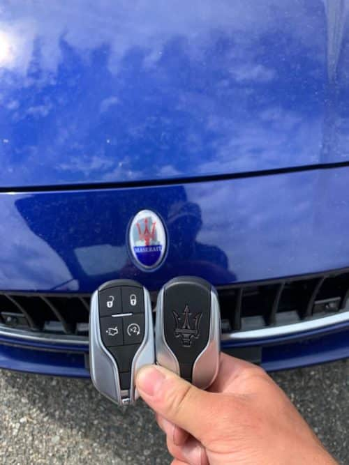 Two new Mazerati key fobs being held in front of a blue Maserati.